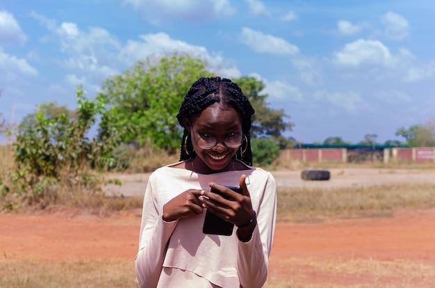 彼女の携帯電話を喜んで操作している美しいアフリカの女性のクローズアップ