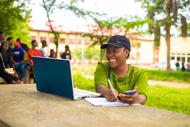 興奮して学校のキャンパスで勉強している美しいアフリカの女性のクローズアップ