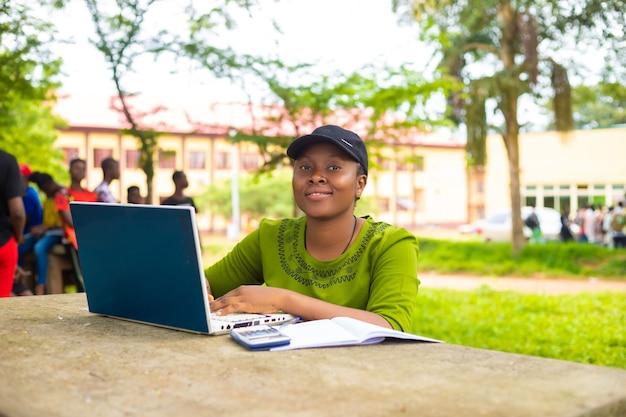 学校のキャンパスで勉強している美しいアフリカの女性のクローズアップ