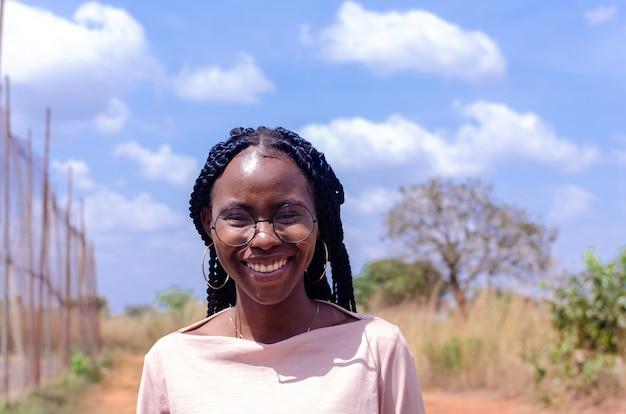 笑顔の眼鏡をかけている美しいアフリカの女性のクローズアップ