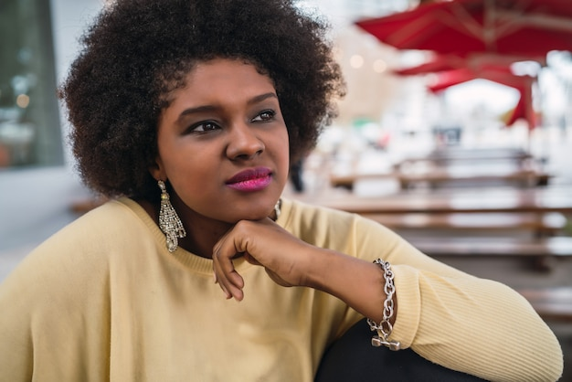 Конец-вверх красивой афро американской латинской женщины сидя на кофейне.