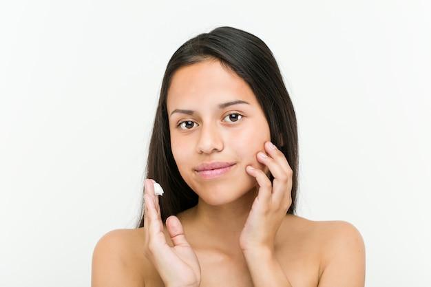 Крупным планом красивой и естественной испаноязычные молодой женщины, применяя увлажняющий крем