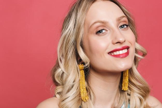 Крупным планом красивая блондинка с ярким макияжем позирует на красном фоне