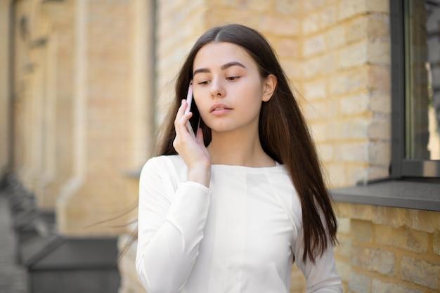 Крупный план красивой девушки в белом с длинными волосами, говорящей по мобильному телефону во время прогулки по улице