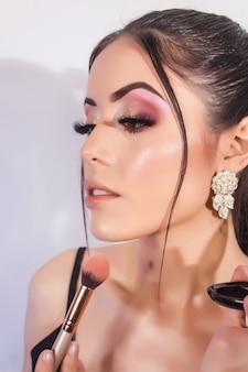 Крупный план красивой девушки с безупречной кожей и кистью для макияжа.