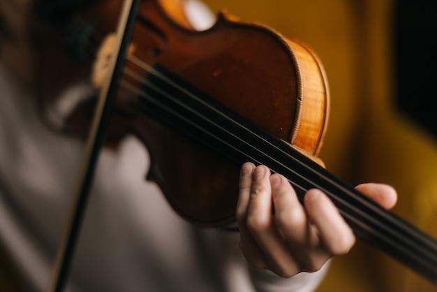 Крупный план красивой скрипки, которую играет девушка. красивая молодая женщина-музыкант, играющий на скрипке