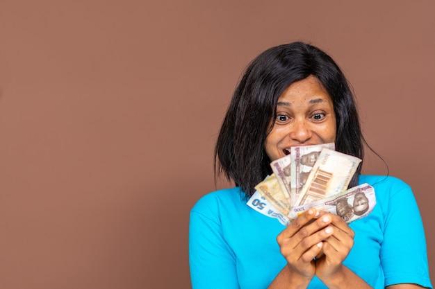 그녀의 손 깜짝 얼굴 개념에 약간의 돈을 들고 아름 다운 젊은 아프리카 여자의 클로즈업