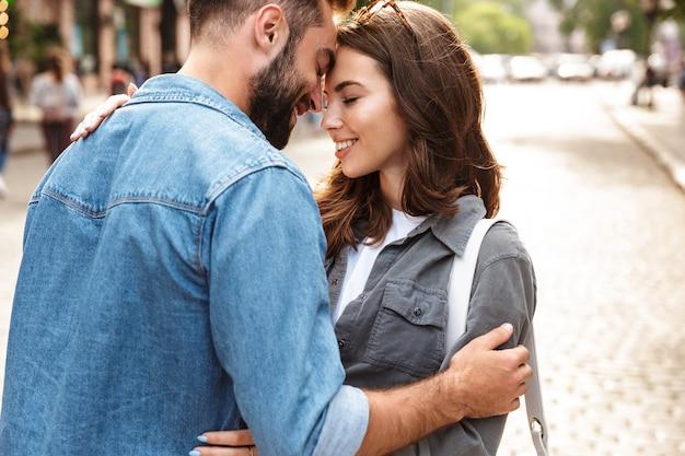 街の通りで、抱き締めて、屋外で恋をしている美しい若いカップルのクローズアップ