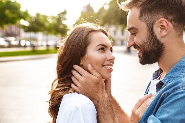 街の通りで屋外を歩いて、抱きしめて愛の美しい若いカップルのクローズアップ