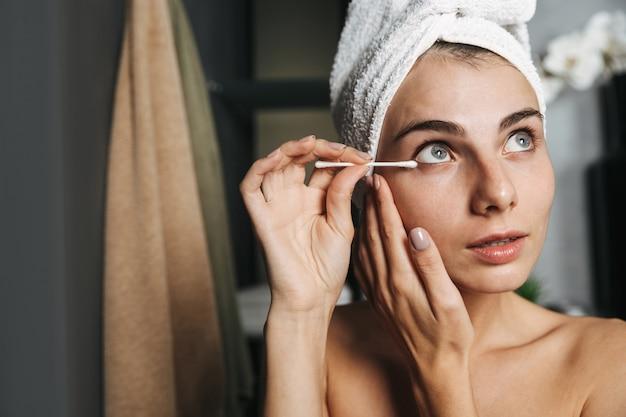 バスルームで綿棒で耳を掃除する彼女の頭の周りにタオルを巻いた美しい少女のクローズアップ