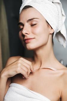 Крупный план красивой молодой девушки с полотенцем, обернутым вокруг головы, касающейся ее кожи пером в ванной комнате