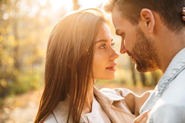 秋の公園で時間を過ごしながら抱きしめる愛の美しい若い幸せなカップルのクローズアップ