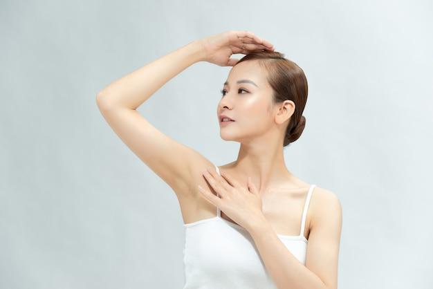 Крупный план красивой молодой женщины, показывающей ее гладкую подмышку, изолированную на белом фоне