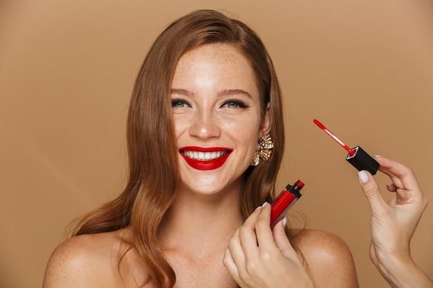 化粧とジュエリーアクセサリーを身に着けている美しい若い女性のクローズアップは、ベージュの壁に孤立してポーズ、化粧を取得します。