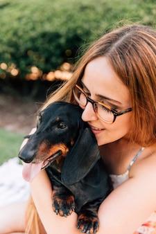 彼女の犬と美しい若い女性のクローズアップ