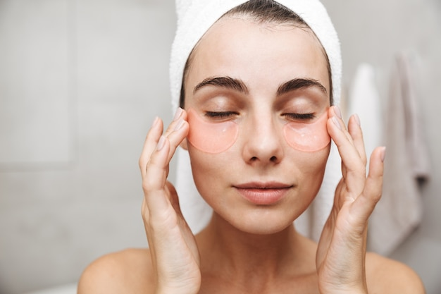 Крупным планом красивая молодая женщина с полотенцем на голове, стоящая в ванной, накладывая повязки на глаза