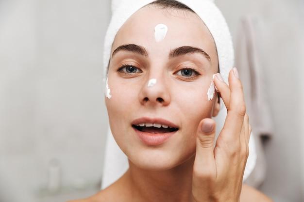 얼굴 크림을 바르고 화장실에 서있는 그녀의 머리에 수건으로 아름다운 젊은 여성의 닫습니다