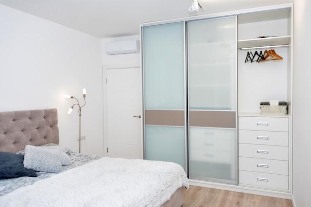 Закройте кровать с цветными подушками, покрывало и уютная лампа.