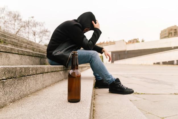 Крупный план пивной бутылки на полу, пьяный молодой человек плачет, испытывает проблемы и испытывает стресс. концепция социальной проблемы молодежи.