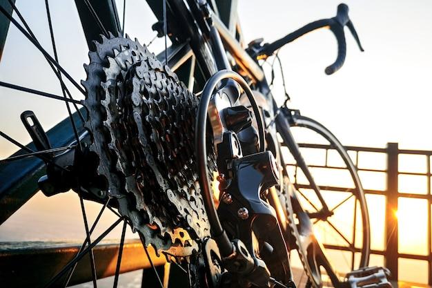 朝の日の出のギアの詳細と自転車ホイールの近く Premium写真