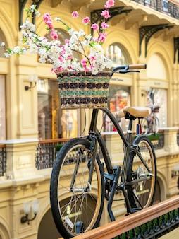 ショッピングセンターで花のバスケットと自転車のクローズアップ。インテリアの美しい装飾要素。
