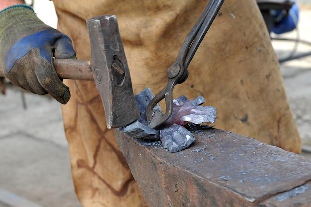 鍛冶屋のクローズアップハンマーとトングで鉄製品を鍛造手作りのコンセプト