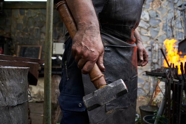 ハンマーを持っている鍛冶屋の手のクローズアップ