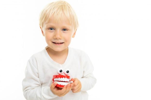 Крупный белокурый ребенок мужского пола с игрушкой в виде белой зубной челюсти на белом фоне