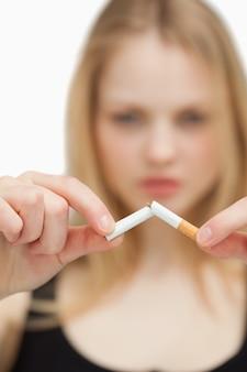 담배를 끊는 blonde-haired 여자의 클로즈업