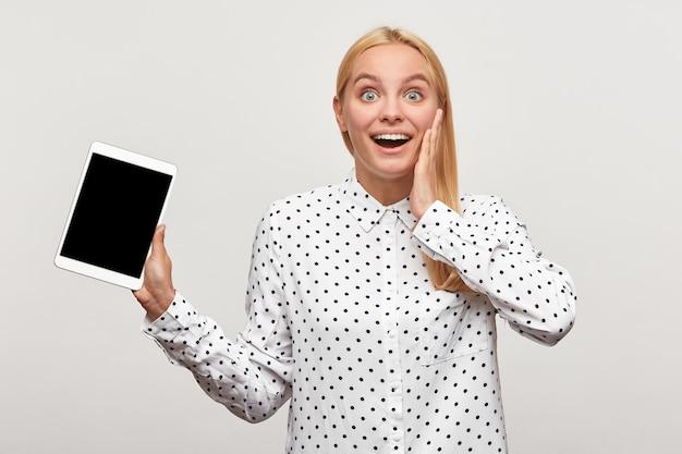 Крупным планом блондинка молодая женщина выглядит счастливой и взволнованной с планшетом в руке, одной рукой придерживая ее за щеку