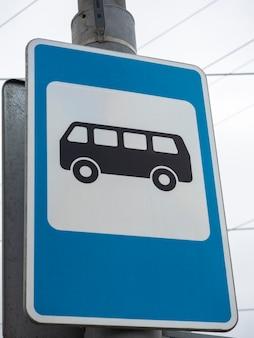 파란색 버스 정류장 표지판의 클로즈업입니다. 세로 사진, 도로 정보 표지판