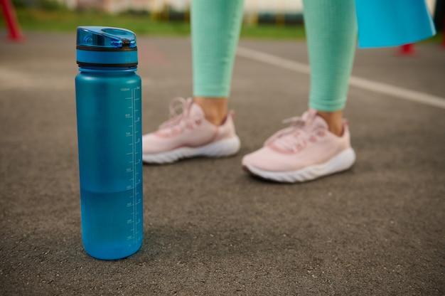 Крупный план голубой пластиковой бутылки с пресной водой на асфальте спортивной площадки рядом с ногами спортивной женщины. концепция ухода за здоровьем и телом