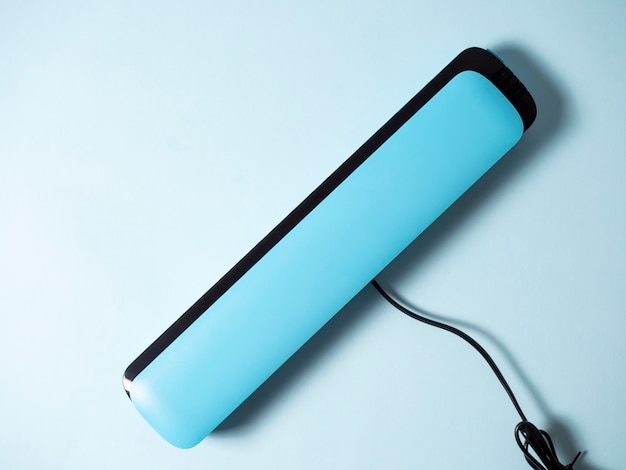 明るい青色の背景に分離された青い真空パッカーのクローズアップ。製品の鮮度を保つための機械。フラットレイ、上面図。