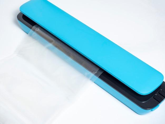 明るい青色の背景に分離された青い真空パッカーのクローズアップ。パッケージがマシンに挿入されます。製品の鮮度を保つためのツール。フラットレイ、上面図。