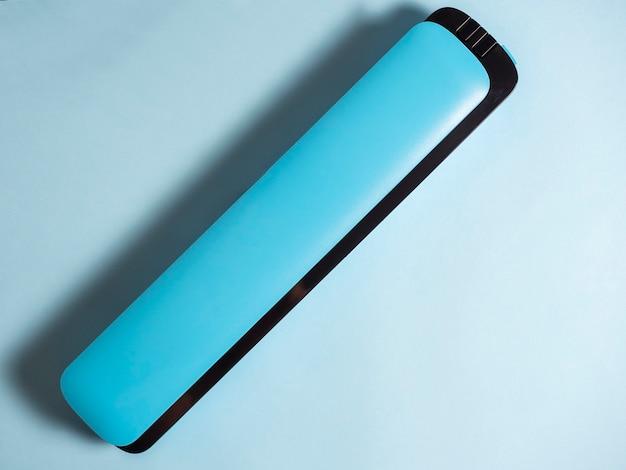 明るい青い壁に分離された青い真空パッカーのクローズアップ。製品の鮮度を保つための機械。フラットレイ、上面図。