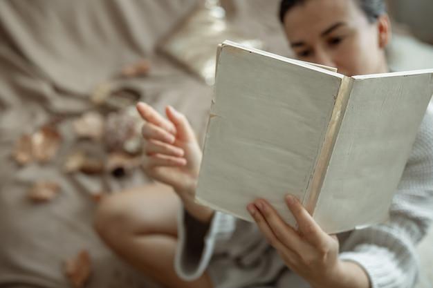 흐린 배경에 있는 여자의 손에 있는 책의 클로즈업.
