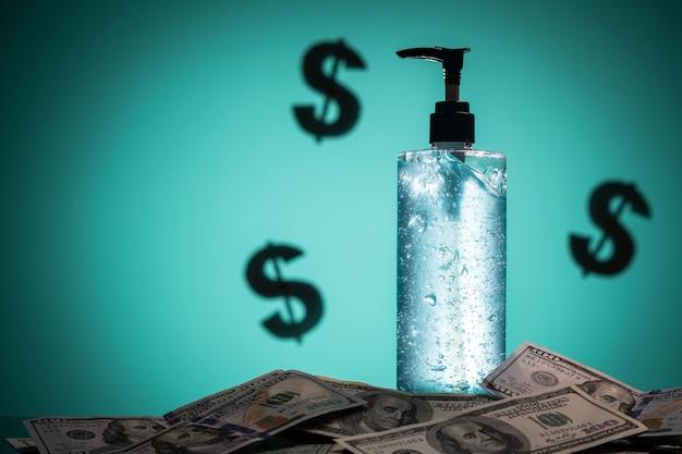 Крупный план бутылки с антисептическим гелем, стоящей на долларовых купюрах.