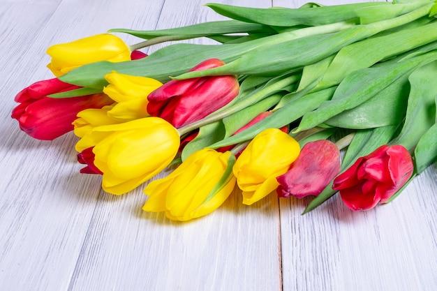黄色と赤の春のチューリップの花束のクローズアップは、木製の光の表面を持つテーブルの上にあります。