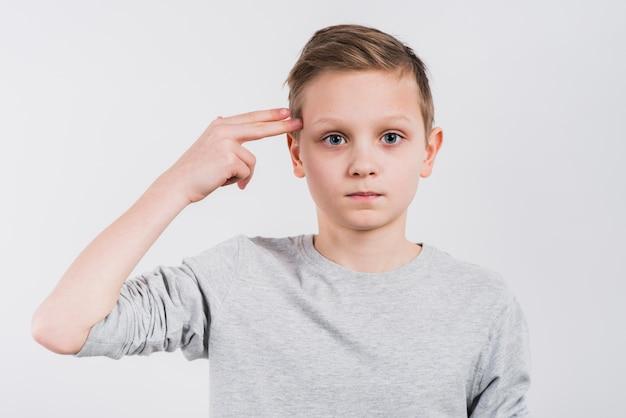 灰色の背景に対してピストルまたは銃のジェスチャーを作る男の子のクローズアップ