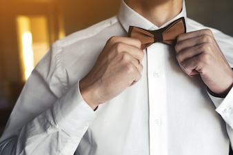 Close-up of a boyfriend arranging his bow tie