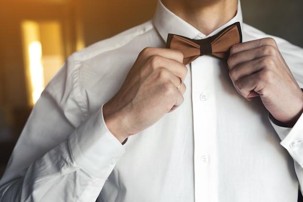 그의 나비 넥타이를 준비하는 남자 친구의 근접 촬영