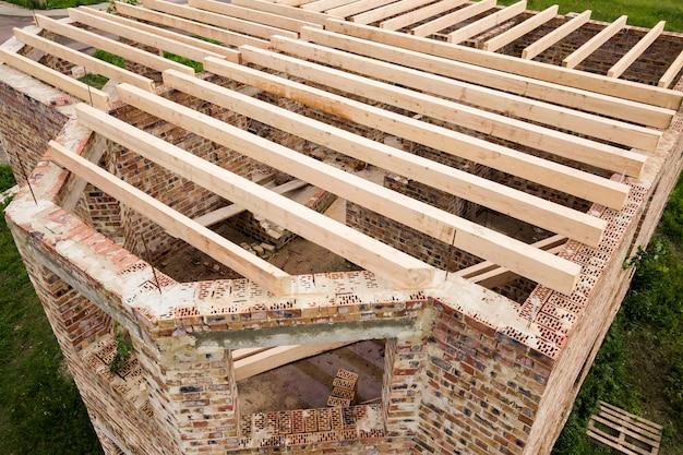 建設中の木製の天井フレームとれんが造りの家のクローズアップ
