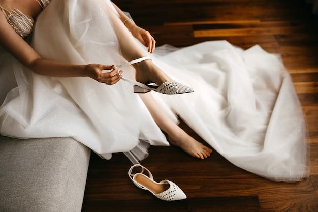 平らな結婚式の靴を履いて、白いドレスを着た花嫁のクローズアップ