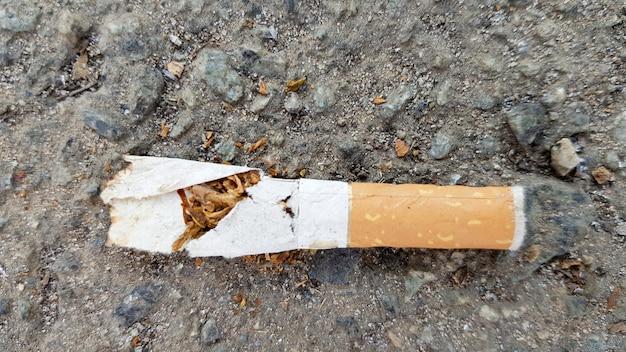 コピースペースのあるアスファルトの壊れたたばこの吸い殻のクローズアップ。国際禁煙デー。タバコ、ニコチン、タバコに対する世界デー