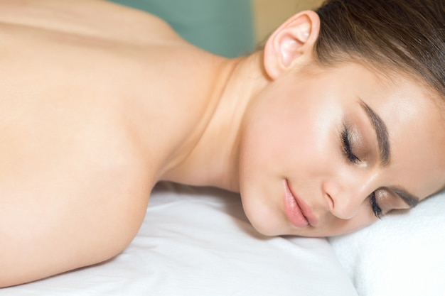 Крупным планом брюнетка улыбается женщина расслабляющий с закрытыми глазами.
