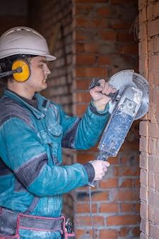 Строитель в защитном шлеме на рабочем месте работает с режущим инструментом.