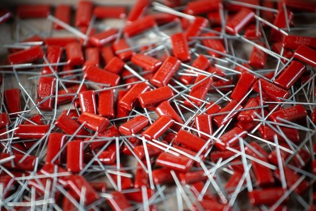 Крупный план красных конденсаторов, расположенных друг над другом на заводе по производству оргтехники и компьютеров. понятие о качественных деталях. партия конденсаторов оптом