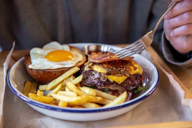 Крупный план бургера из двух половинок в тарелке с картофелем фри.