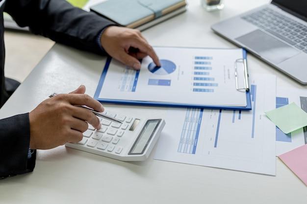 Крупный план делового человека, использующего белый калькулятор, финансового бизнесмена, изучающего числовые данные в финансовом документе компании. он использует калькулятор для проверки точности чисел.