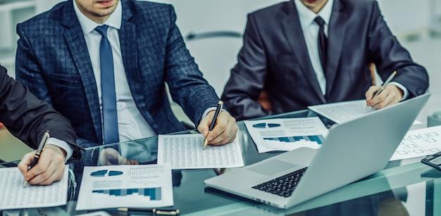 オフィスの職場でマーケティングレポートの分析を行っているビジネスチームのクローズアップ。